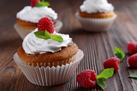 Delicious cupcakes with berries and fresh mint on wooden table close up