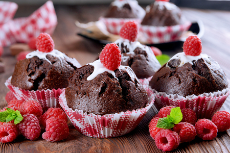 Delicious chocolate cupcakes with berries and fresh mint on wooden table close up Stock Photo