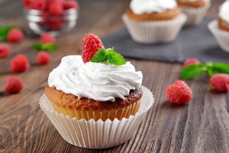 Delicious cupcake with berries and fresh mint on wooden table close up