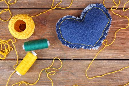 Denim heart and thread on wooden background