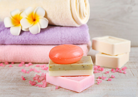 Bars of natural soap and colorful towels on light background 版權商用圖片