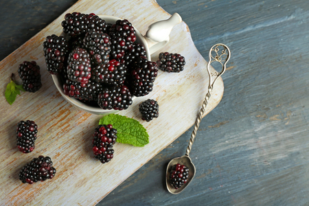 Heap of sweet blackberries with mint in cup on table close up Stock fotó