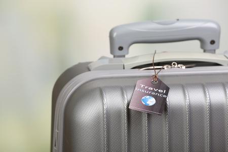 Koffer met reisverzekeringsetiket op lichte onscherpe achtergrond