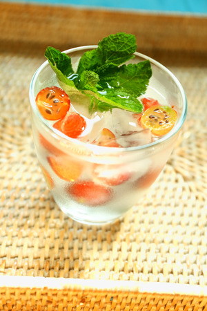 Glass of cold refreshing summer drink with berries and ice cubes on table close up Standard-Bild