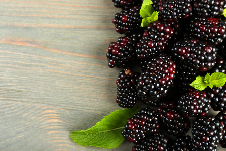 Heap of sweet blackberries with mint on wooden table close up Stock Photo