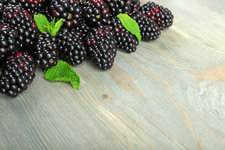 Heap of sweet blackberries with mint on wooden table close up Stock fotó