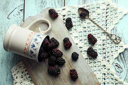 Heap of sweet blackberries in cup on table close up