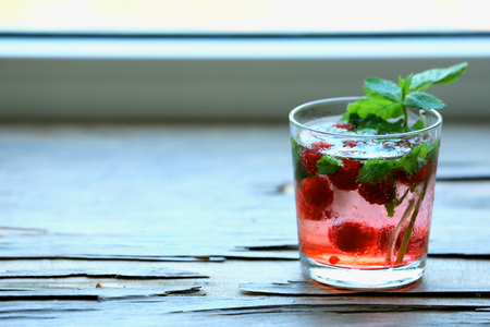 Glass of cold refreshing summer drink with berries and ice cubes on table close up Stock Photo