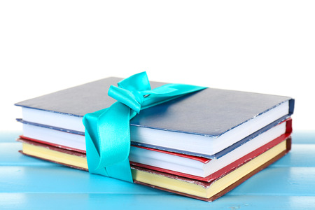 Stack of books with ribbon on table isolated on white
