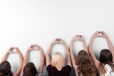 Young people makes hearts using fingers on light background 스톡 콘텐츠 - 102139392
