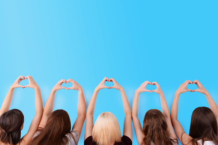 Young people makes hearts using fingers on light background