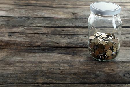 Coins in money jar on wooden background