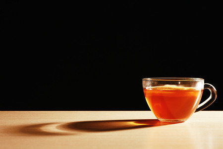 Glass cup of tea with piece of lemon on wooden table on black background Stock Photo