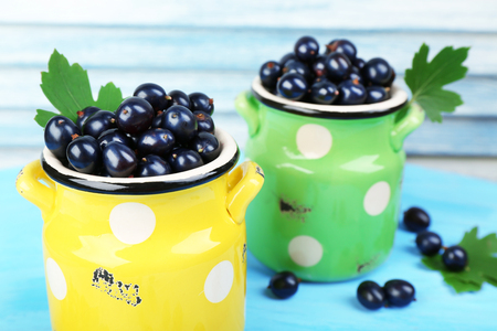 Ripe black currants in metal mugs on wooden background Stock Photo