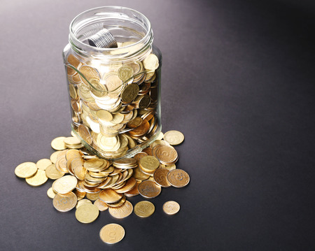 Glass jar with coins on dark background Stock Photo