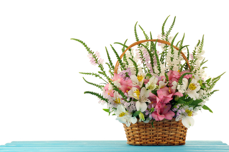 Beautiful floral arrangement in basket isolated on white