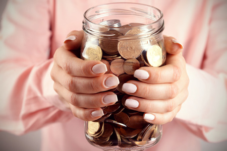 Woman holding money jar with coins close up Archivio Fotografico - 102232536