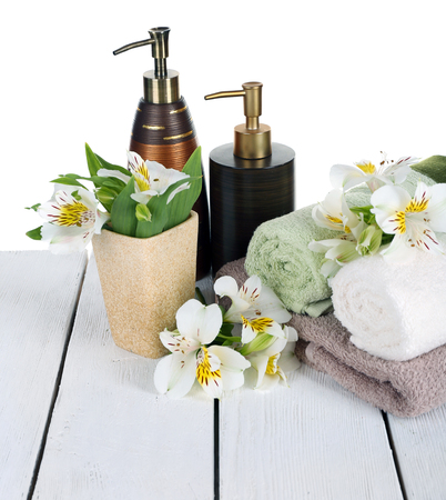Soft towels with dispenser and flowers isolated on white Stock Photo