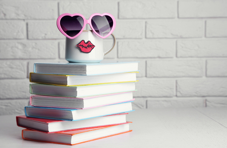 Books and cup with lips on wooden table on brick wall background