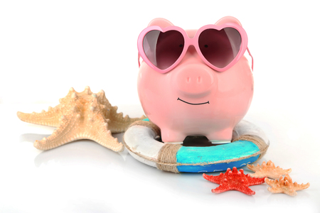 Pink piggy bank in sunglasses with starfishes and lifebuoy isolated on white Zdjęcie Seryjne