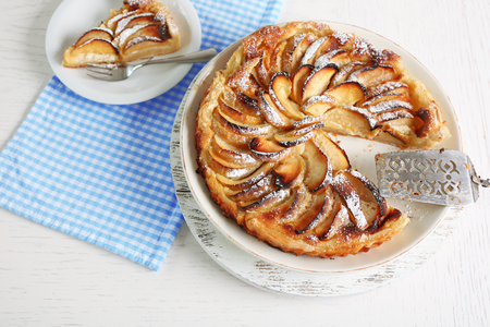 Homemade apple pie on cutting board and fresh apples on wooden background