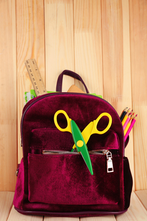 Backpack with school supplies on wooden background Banco de Imagens