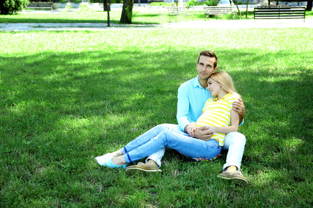 Young pregnant woman with husband sitting on green grass in park 免版税图像