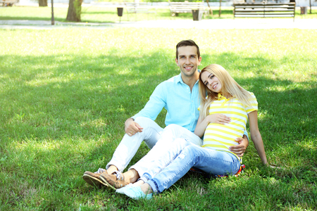 Young pregnant woman with husband sitting on green grass in park Stok Fotoğraf