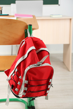 Backpack with knife in classroom, close up. Juvenile delinquency 스톡 콘텐츠