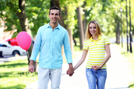 Young pregnant woman with husband walking outdoors