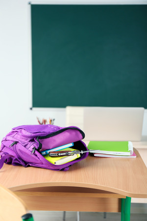 Backpack with knife in classroom, close up. Juvenile delinquency Stock Photo