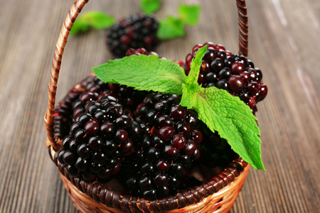 Ripe blackberries with green leaves in wicker basket on wooden table, closeup