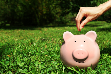 Female hand putting coin into pink piggy bank over green grass background