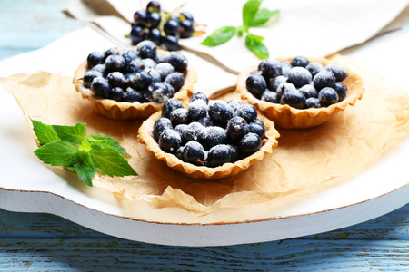 Delicious crispy tarts with black currants on parchment on wooden board, closeup 写真素材