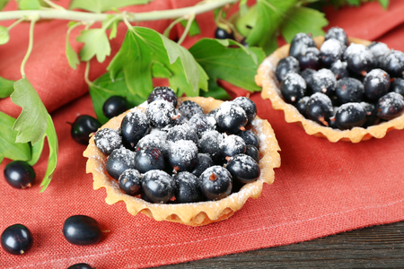 Delicious crispy tarts with black currants on red napkin, closeup Foto de archivo