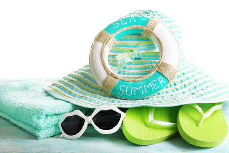 Summer accessories on wooden table isolated on white