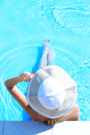 Woman in hat resting in swimming pool