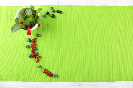Group of summer berries with mint on green tablecloth background Stock Photo