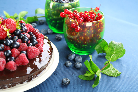 Delicious chocolate cake with summer berries on blue tablecloth, closeup