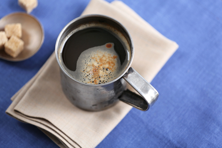 Metal cup of flavored coffee with lump sugar and flowers on table with napkin, closeup Archivio Fotografico