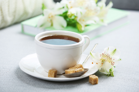 Cup of coffee with lump sugar and flowers on sofa Archivio Fotografico