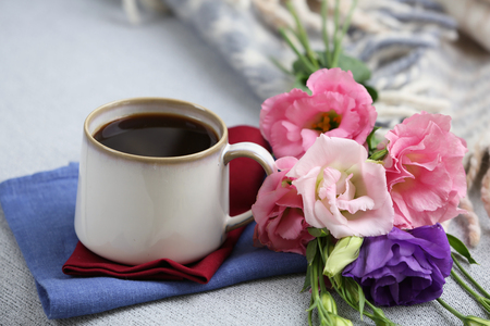 Cup of coffee with flowers near books on sofa in room Archivio Fotografico