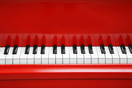 Piano keys of red piano close up