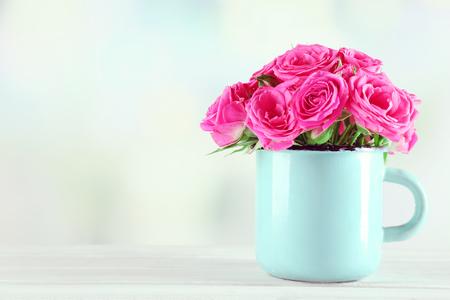 Beautiful roses in mug on bright background Stock Photo