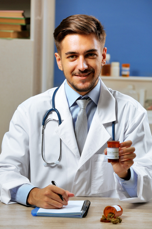 Doctor holding bottle with medical cannabis close up