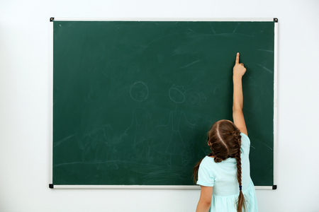 Little girl pointing at something at black chalkboard in classroom Stock Photo