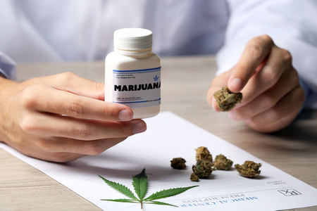 Doctor hand holding bottle with medical cannabis close up Stock Photo