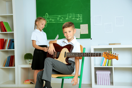 Cute pupils having music lesson in classroom at elementary school Foto de archivo