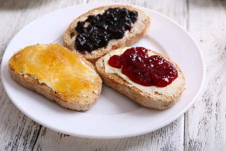 Fresh toast with butter and different jams on table close up Фото со стока