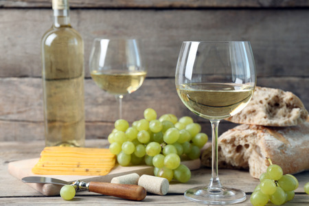 Still life of wine, grape, cheese and bread on rustic wooden background Standard-Bild